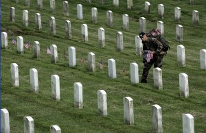 Sgt. Timothy Davis of San Diego places American flags before the gravestones of those buried at Arlington Cemetery.