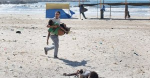 A boy on a Gaza beach killed in an Israeli attack is carried away.